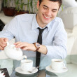Smiling young men pours tea into a cup. Beautiful smile - Stok fotoğraf