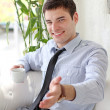 Handsome guy drinks tea, and extends a hand — Stock Photo