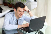 Smiling men think and work at the laptop — Stock Photo