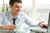 Young man with cup looking at the laptop — Stock Photo