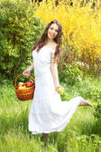 Beautiful girl with bast basket and apples on the nature — Stock Photo