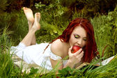 Young woman with red hair eat red apple on the nature — Stok fotoğraf