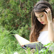 Young beautiful girl reading a book outdoor — Stock Photo #5731144