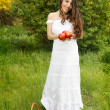 Beautiful girl with a basket in white dress holding a red apple — Stockfoto