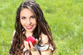 Beautiful young woman with red lips and long hair present red ap — Stock Photo