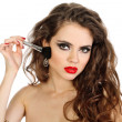 Hairstyle. Beautiful young woman with a make-up brush isolated o — Stock Photo