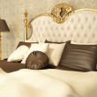 Luxurious bed with pillows and standing lamp in royal interior — Stock Photo