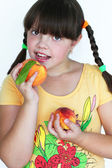 Happy Beautiful little girl holding tasty peaches — Stock Photo