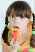 Young beautiful girl eating orange peach — Stock Photo
