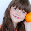 Smiling little girl with orange, happiness — Stock Photo