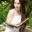 Young beautiful girl reading a book outdoor - Photo