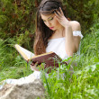 Young beautiful girl reading a book outdoor — Stock Photo