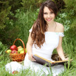 Smiling beautiful woman read the book on the nature. garden — Stock Photo #6649849