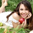 Royalty-Free Stock Photo: Portrait a pretty young women with red apple on the green field