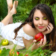 Portrait a pretty young women with red apple on the green field — Stock Photo