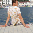 Handsome man relaxing, sitting on the pier near sea, looking on — Stock Photo #6650122