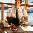 Handsome man businessman work at the laptop in restaurant — Stock Photo
