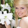 Happy Smiling blonde young woman with white lily, nature — Stock Photo #6652490