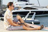 Empresário bonitão executando um laptop na costa perto da yach — Foto Stock