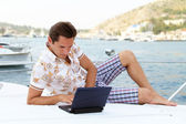 Handsome businessman lying on a yacht and working on a laptop — Stock Photo