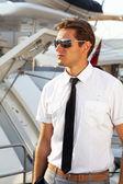 Knappe man, een ernstige kapitein in een wit overhemd in de buurt van het jacht, op zoek van aw — Stockfoto