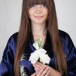 Portrait of a beautiful oriental girl with a flowers in the hand — Stockfoto
