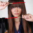 Japanese Geisha with red chopsticks — Stock Photo #6667409