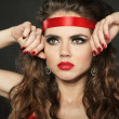 Attractive woman with red ribbon on the head on black background — Stock Photo