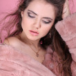 Fashion young woman wearing winter fur coat posing on pink backg — Stock Photo