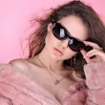 Fashion young woman wearing winter fur coat posing on pink backg — Stock Photo #6669235