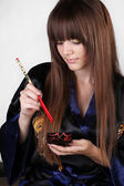 Beautiful woman holding red chopsticks isolated on grey backgrou — Stock Photo