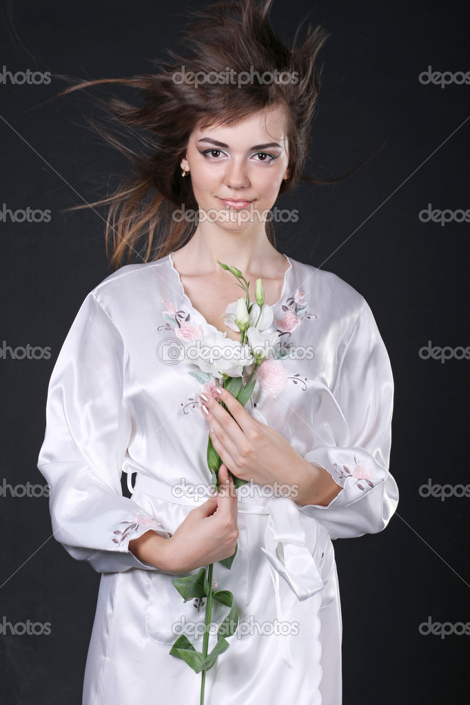 Beautiful woman in oriental robe with flowers isolated on black interior — Stock Photo #6667169