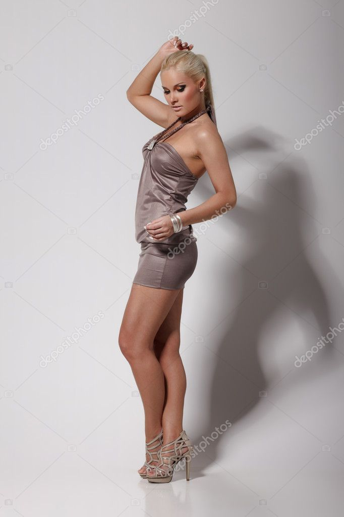 Young blond lady in a dress posing on gray background — Stock Photo #5502828