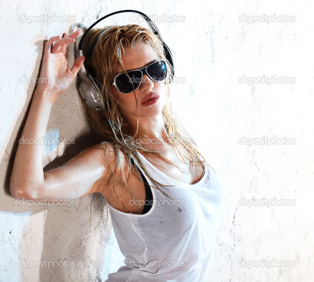 Wet babe in white shirt and sunglasses listening for the music using headphones  Stock Photo #5593144