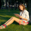 Young Woman Uses Tablet PC In The Park — Stock Photo