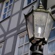 An old-fashioned street lamp in front of a typical German facade - Stock Photo
