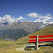 Red bench overlooking the beautiful mountains — Stock Photo