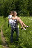 Man carry woman on hands on summer meadow — Stock Photo