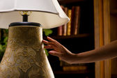Night lamp touched by female hand — Stok fotoğraf