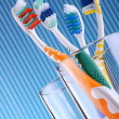 Composition with four toothbrushes on blue background - Stock Photo