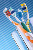 Composition with four toothbrushes on blue background — Stock Photo