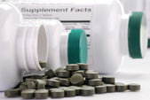 Dietary supplement tablets and containers — Stock Photo