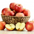 Apples and wicker basket isolated on white — Stock Photo
