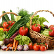 Composition with raw vegetables and wicker basket - Stockfoto