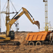 Постер, плакат: Backhoe loading a dump truck