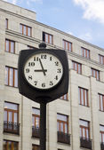 Horloge de rue en face d'un bâtiment — Photo