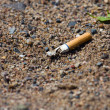 Smoked cigarette on a ground — Stock Photo