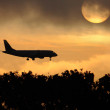 Stock Photo: Silhouette of the big plane on a runrise background