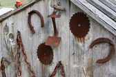 Antique farm tools on a shed wall — Stock Photo