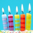 Five birthday candles on blue background — Stock Photo